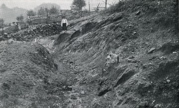 Geological Survey.  Man stands near a cut in the hillside.