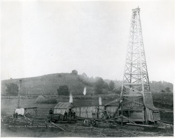 'Burning off the gas from an oil well in Ritchie County.  This is a wood derrick. The flaming torches are to remove the gas out of the oil; a waste that isn't occurring today; it is too precious.'