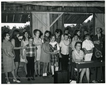 'In 1969 a group representing Webster Springs Grade School sang 'The Webster County Hills' in the pavilion of the Point Mountain Reunion.  This was the first time a school was represented at the annual meeting.  Front row, left to right: William Gregory, Gloria Miller, Debra Hamrick, Michael Gregory, Jeffrey Cochran, Jack Cochran.  Second Row:  left to right: Mrs. Winnie Belasco, Vickie Hamrick, Kathy Adams, Karen Hamrick, Vickie Williams, Diana Marsh, Adola Cogar, Martha Schrader, Susan Cummings, Principal Walter Hall, Miss Virginia Dyer played for the group.  Thomas B. Bickel wrote the lyrics.  Gordon T. Hamrick took the photo. --Berlin B. Chapman.  The Annual Point Mountain Reunion in Webster County exemplifies an important organization in central West Virginia.  It began in 1928 and was known as the 'Hamrick-Gregory Reunion.'  For decades hundreds of people have assembled for visiting and for a program featuring local talent.  There is a pavilion, monument, and well-kept grounds.  it is an all-day meeting with picnic dinner, held on the fourth Sunday in August.  'The Webster County Hills' is in Sampson N. Miller, Annals of Webster County, pp. 370-371.  See also, Mayme H. Hamrick, The Hamrick and Other Families, pp. 107-109.  Trophies are awarded to the senior lady; senior gentleman; couple longest married; and to the party coming the greatest distance to the reunion.  See 'The Call of the Ole Elk Country', S. N. Miller, Annalls, pp. 372-373.  This picture is in Webster Echo, 3/27/85, page 19.  A copy of photo was presented to Principal Walter Hall, ibid, 5/13/70.' Part of the lyrics for the song the children are singing are as follows:  'Where the gray fox and the red give the hunting dogs a chase, and the rabbit runs so swiftly that he always leads the race.'