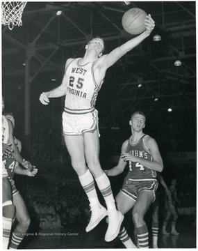 West Virginia University Basketball player, Bob Benfield, number 25, in mid air, reaches for a rebound in a game against St. Johns.