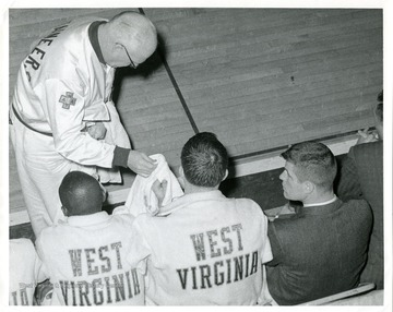 West Virginia University Basketball Trainer Whitey Gwynne is handing out towels to players sitting on the bench. 'Taylor Publishing Company, Job Number 07206, Picture Number 2, page 209.'