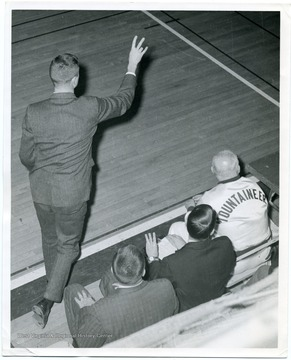 West Virginia University Basketball Coach Bucky Waters is signaling plays to his players, while Assistant Coach Sonny Moran, an unidentified coach, and Whitey Gwynne, the trainer looks on from the bench.