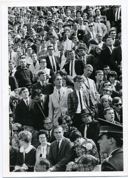 Students cheering on the Mountaineers during a football game. 'Taylor Publishing Company, Job Number 07206, Picture Number 38a, Page Number 254, West Virginia University, Morgantown, West Virginia.'