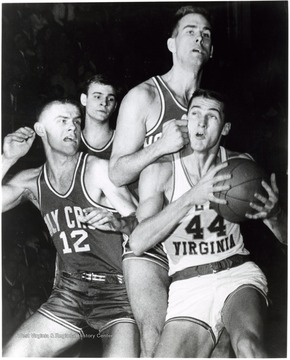 Jerry West is fouled by Ralph Brandt in attempting a lay- up against Holy Cross. Number 12 is George Blaney.