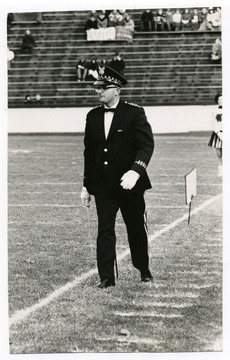 Budd Udell is entering the field to direct the band at a football game.