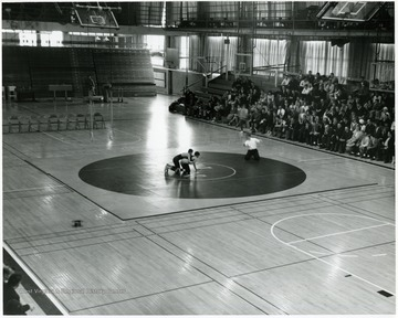 Two people wrestle in the center of a gym with a crowd watching.