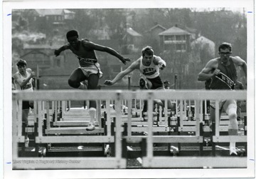 Track members of West Virginia University and Virginia Tech compete in the hurdles.