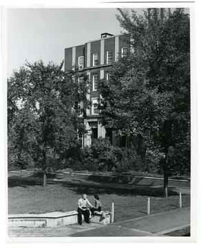 Couple is sitting in front of the Chemistry Building, Clark Hall, West Virginia University.