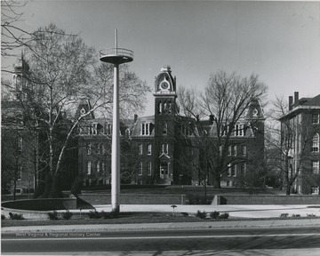 Woodburn Circle is pictured in the background. The mast is erected in Memorial Plaza, which is located directly in front of Oglebay Hall.