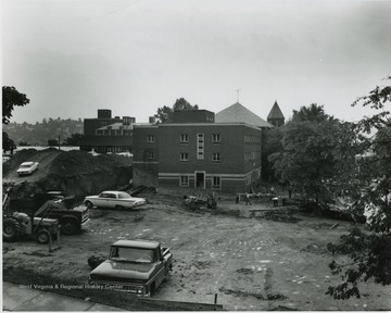 View of buildings on University Avenue, opposite E. Moore Hall, etc.  Cafeteria building destroyed, Health Center building being moved to where former stood.  Background- Main library, Chemistry, shops, Reynolds, Administration building.