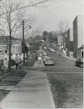 View of students walking around North High Street.  Fraternity houses on left side of street.  Ruins of Mechanical Hall II on front left.  Girls dorm, Boreman, on right.  Men's Halls, later changed to Boreman when girls were to live in them.