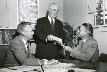 Leroy Myers, right, graduate student at Michigan State University, has received a $3,000 annual fellowship for study in the field of city planning and urban renewal, according to Harold W. Lautner, left, head of the M.S.U. department of landscape architecture and urban planning. On behalf of the donor, the Sears-Roebuck Foundation, J.J. Roden, manager of the Sears store in Lansing, Mich., presents the fellowship certificate to Myers. An assistant professor of geography at West Virginia University, Myers will do advanced study at M.S.U. for the coming two years. Four other individuals studying city planning and urban renewal at other universities received similar awards.