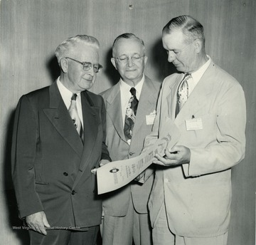 'J. D. Ferguson, president and editor of The Milwaukee Journal; Director P.I. Reed of The West Virginia University School of Journalism; Elmer G. Trotzig, head of the Department of Journalism, University of South Dakota, Vermillion. Prof. Trotzig as president of the American Society of Journalism and School Administrators presents to Mr. Ferguson for The Milwaukee Journal the sixth annual citation of ASJSA which recognized the newspaper for its honesty, courage, and persistence in reporting of world events. Director Reed, Who looks on, was chairman of the ASJSA Committee on Awards. The presentation took place August 28, 1951, at the Lincoln Avenue resident hall of the University of Illinois, Urbana, as part of the program of the Association for Education in Journalism.'