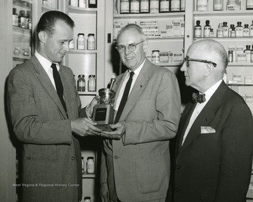 'Left to right, unknown, Dean J. Lester Hayman, College of Pharmacy; F. M. Dent, McVicker`s Pharmacy.'