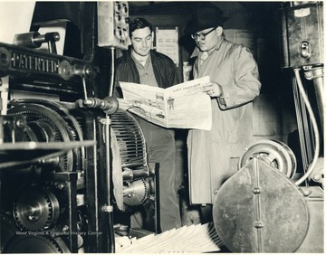 Two men looking at a copy of the Daily Athenaeum.