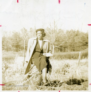 Portrait of African-American student, Mary Dodson, seated on a tree stump.
