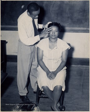 African-American teacher examines an African-American student's face.