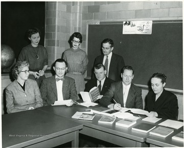 A group of individuals in a room with a display of books.  Some are seated and some are standing and engaged in a conversation.  Standing, third from left, Clifford Brown.  Seated, left to right, Grace Scott, Eston K. Feaster, rest unknown.
