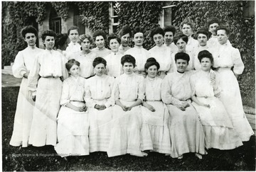 The picture shows a group of female students in front of a ivy covered building with a front arched entrance.