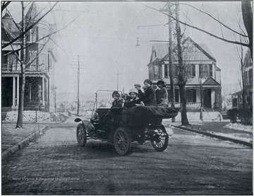 Female students riding in a Model T at the intersection of Pleasant and Spruce Streets.