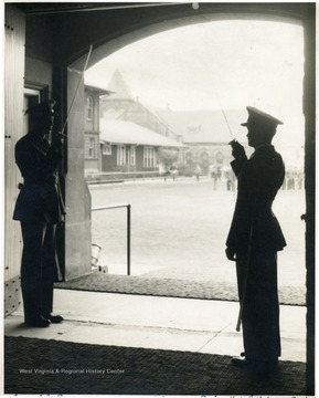 Two males in military uniform salute with saber held upward to the shoulder on an atrium of the building.  The caption on the original reads 'Cadet Col. Barnes. - Regimental Adjustment Ewing'.