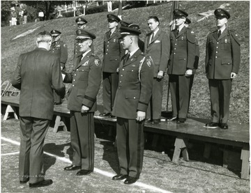 'Major General Ralph W. Zwicker presents Dept. of Army Civilian Award of Appreciation to Dr. Irvin Stewart, former University President at brigade ceremony on drill field.  President Stahr in civilian clothes on reviewing stand.'