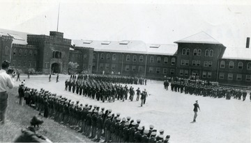 Cadets march in formation in Drill Field with Armory and Mechanical Hall in the background.