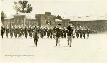 Cadets with a gun on shoulder march on the Drill Field. There are three saluting cadets leading the rest.