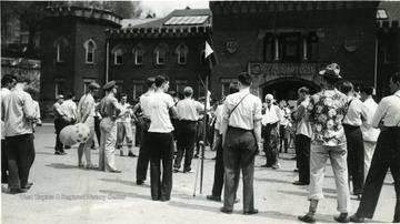 The R.O.T.C. band performs in front of Armory while onlookers listen.