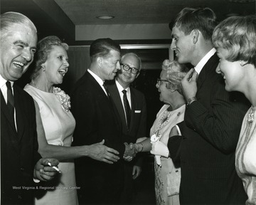 'Scene from the 100th Anniversary reception honoring Dr. and Mrs. Harry B. Heflin.  From left to right are shown: Ralph Bean, president of the WVU Board of Governors; Mrs. Heflin; Dr. Heflin; Donovan H. Bond, Exec. Dir of the 100th Anniversary observance; Mrs. Clifford Brown; David C. Hardesty, former president of the WVU student body; and Susan Brown Hardesty, Mrs. David Hardesty.