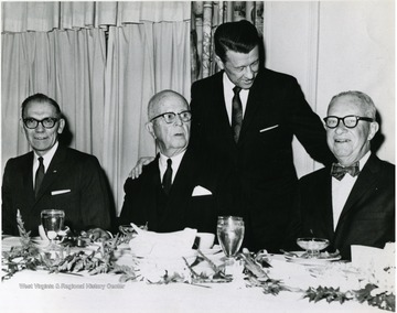 Dr. Harry Heflin is standing and on the left is Martin Piribek, the president of First National Bank.