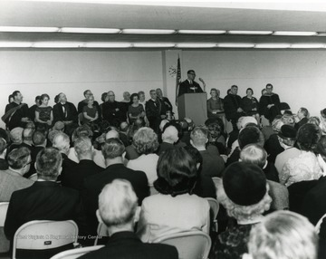 Harry Heflin speaks to a crowd. President Irvin Stewart sits behind podium second to left from a speaker.