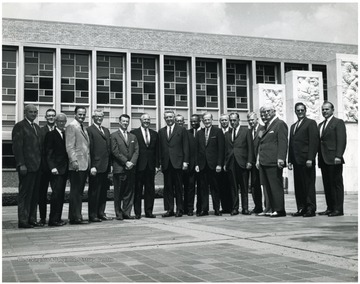 'Left to right: E.J. Nesius, Director of Application Center; Robert F. Munn, Provost and Librarian (in back); Rey Smith, State Superintendent of Schools; Don Robertson, Attorney General; Robert Baily, Secretary of State (W. Va.); Harry Heflin, Acting President of WVU; Hulett Smith, Governor; four unknown people; Denzil Gainer, State Auditor; three unknown people; William McMillion, Comptroller; Harold Shamberger, Assistant to President of University.'