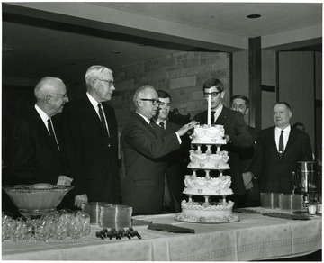 'Scene at the reception in the Mountainlair honoring the close of the 100th Anniversary year on Feb. 7, 1968 shows, from left to right: Maurice Brooks, prof. of forestry and wildlife management and a member of the 100th Anniversary executive committee; Festus Summers, University historian; Donovan H. Bond, exec, dir. of the 100th Ann. observance; David Zinn, president of the WVU student body for 1968-1969; Jim Mullendore, president of the WVU student body from 1967-1968; Gus Comuntzis, co-owner of Comuntzis' Restaurant who baked the birthday cake; and Sam Boyd, Jr., prof. and chairman of dram and a member of the 100th Ann. exec. committee.'