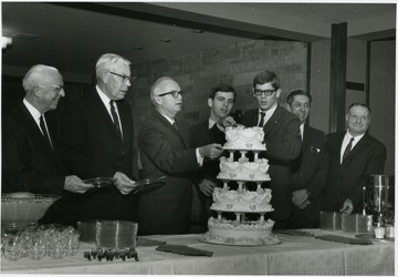 At the reception in the Mountainlair Anniversary executive committees and others surround the WVU's Birthday Cake, from left to right: Maurice Brooks; Festus P. Summers; Donovan H. Bond; David Zinn; Jim Mullendore; Gus Communtzis; Sam Boyd, Jr.