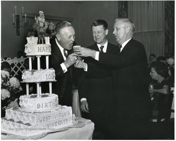 '100th Anniversary Birthday Dinner Cake-Cutting ceremonies.  Left to right are: Gov. Hulett Smith, acting WVU President Harry B. Heflin, and Congressman Arch A. Moore.'