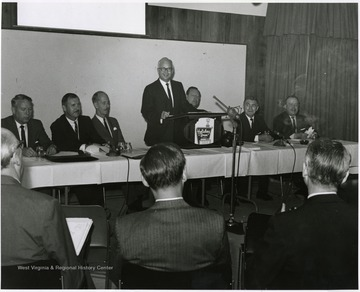 "'Donovan H. Bond, Executive Director of the 100th Anniversary Observance, is seen speaking at the September 12, 1967 seminar, ""The State University.""  From left to right, others include: Keith Glancey, WVU Profesor of Education; Thomas Isaack, WVU Professor of Management; Thomas Canning, WVU Professor of Music; Ruel Foster, WVU Professor and Chairman of English and Chairman of the Seminar Planning Committee; Peter Muirhead, Associate U.S. Commissioner of Education; and James G. Harlow, President of WVU.'"