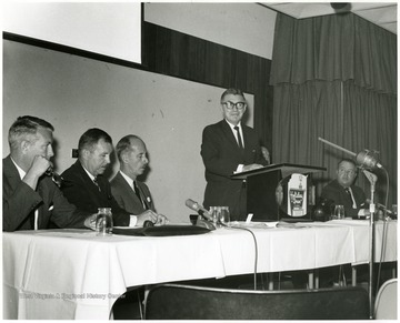 'Peter Muirhead, associate U.S. commissioner of Education, is shown speaking at the Sept. 12, 1967 seminar on 'The State University.'  Also shown, from left to right, are: Keith Glancey, WVU Prof. of Education; Thomas Isaack, WVU Prof. of Management; Thomas Canning, WVU Prof. of Music; Ruel Foster, WVU Prof. and Chairman of English and Chairman of the semnar planning committee; and James G. Harlow, president of WVU.'