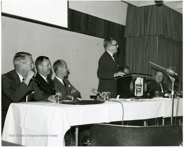 "'Peter Muirhead, associate U.S. commissioner of education, is shown speaking at the Sept. 12, 1967 seminar on ""The State University.""  Also shown, from left to right, are: Keith Glancey, WVU prof. of education; Thomas Isaack, WVU prof. of management; Thomas Canning, WVU prof. of music; Ruel Foster, WVU prof. and chairman of English and chairman of the seminar planning committee; and James G. Harlow, president of WVU.'"