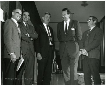 'Chancellor of Vanderbilt University Alexander Heard (second from left) is shown chatting with seminar committee chairman J. Clifford Stickney, WVU prof. of Physiology and Biophysics (left); Robert Stilwell, WVU prof. of German and chairman of Foreign Languages (center); Ruel Foster, WVU prof. and chairman of English (second from right); and George Nocito, WVU prof. and chairman of Art.  Stilwell, Foster and Nocito served as panelists a the Nov. 28, 1967 seminar on the Future of Undergraduate Education at WVU.'