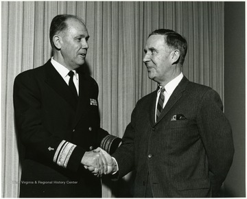 "'Read Adm. James W. Kelly, chief of Naval Chaplains (left), shakes hands with Rev. Joe Gluck, WVU director of Student Affairs at ""Man and His Religions"" Symposium Jan. 7-9, 1968.'"