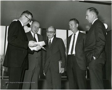 'Dr. Moody Prior, graduate department of English at Northwestern University (center) chats with seminar planning committee chairman John Ludlum, Dean of the WVU Graduate School (left); Homer Evans, Prof. of Agricultural Economics and Associate Director of the WVU Agricultural Experiment Station (second from left); Delmas Miller, WVU Prof. of Education and Chairman of Secondary Education (second from right); and Virgil Peterson, WVU prof. of English, at the Dec. 6, 1967 seminar on the Future of Graduate Education at WVU.'