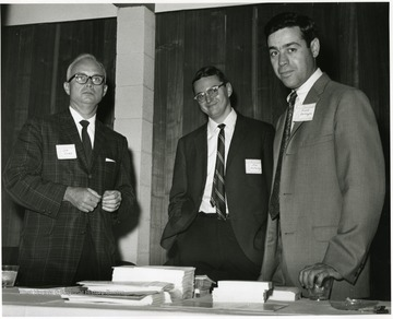 "'Donovan H. Bond, exec. dir of the 100th Ann. observance (left), Jim McCauley, research and graduate assistant of the 100th Anniversary Office (center), and Frank Carlomagno, assistant dir. of the WVU Foundation, Inc. (right) are shown at the ""Man and His Community"" symposium, June 28-29, 1967.'"