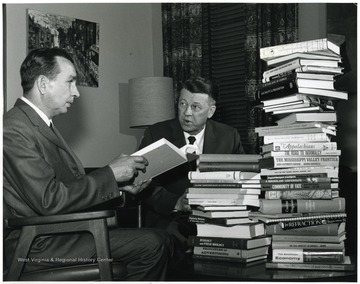 'John Luchok, University editor, (at left) looks over books written by the professors honored at May 11 Authors' Banquet with Dr. Harry B. Heflin, acting WVU President.'