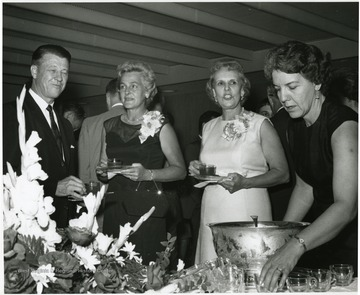 'Scene from the 100th Ann. reception honoring Dr. and Mrs. Harry B. Helfin.  Facing the camera, from left to right, are: Dr. Heflin; Mrs. Gilbert Bachmann, member of the WVU Board of Governors; Mrs. Heflin; and Mrs. Ernest Nesius.'