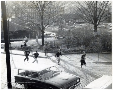 A scene from Greek Week events 'Hill Climb' showing members of Fraternity running up the North High Street.  In the background Administration Building, Old Buildings and Grounds and Security headquarters, Chemistry Building and Armory are also shown.