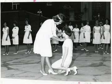 Student kneeling receiving a pin on her chest.
