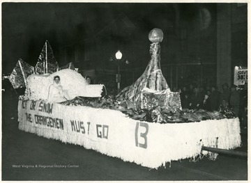 A float in homecoming parade depicting igloo and seal with a reference for an upcoming football game with Syracuse 'Orangemen'.
