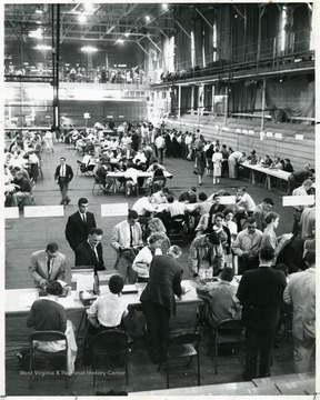 A scene from registration at the Field House: a male in dark suit second from the left at the bottom of picture talking to a seated female in light blouse is WVU Folklorist and Musician Patrick W. Gainer.