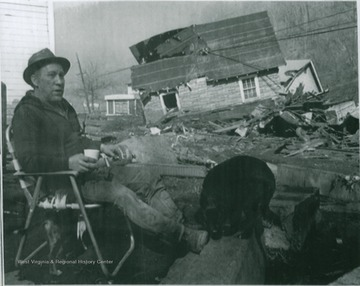 "James Chapman sits with his dog in front of his demolished home three days after the Pittston Coal Company's coal slurry impoundment dam broke, killing 125 people and leaving thousands homeless. Four days before the disaster, the dam had been declared ""satisfactory"" by federal inspectors."